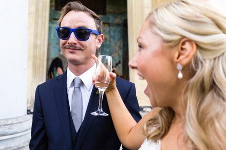 Bride points at groomsman's handlebar moustache whilst he wears sunglasses at Asylum wedding.