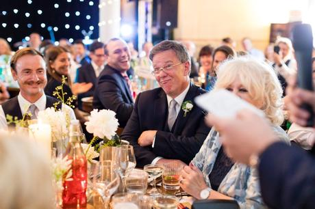 Guest makes funny face during wedding speeches.