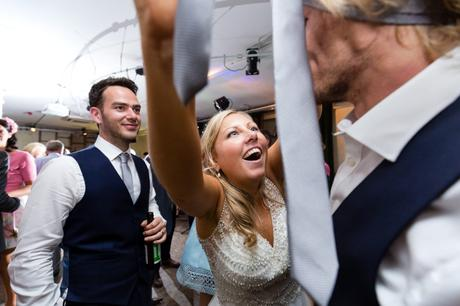 Bride puts tie on guest's head during fun wedding party.