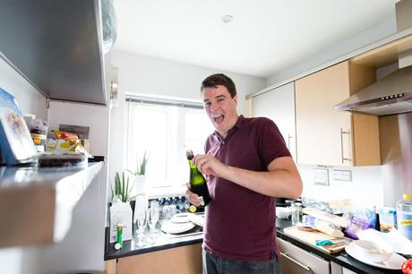 Groomsman smiles when opening champagne bottle.