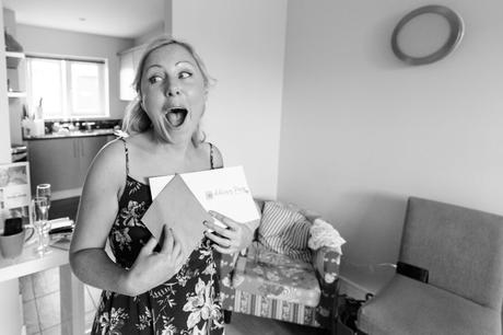 Bride makes happy face when reading card from the groom at Asylum Chapel wedding.