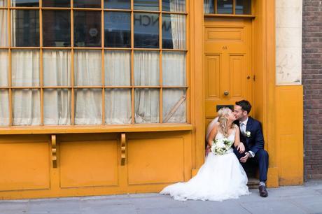 Bride & Groom kissing in doorway in front of yellow London building.