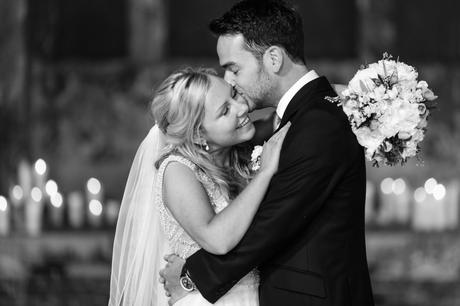 Bride smiles as groom kisses her on the cheek at The Asylum with candles in the background.