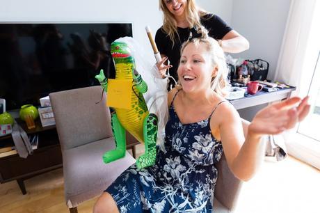 Bride holds blow-up dinosaur with a veil at London Asylum wedding.