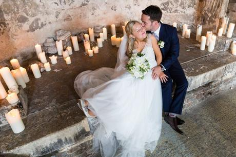 Top-down shot of groom kissing bride encircled in candles at The Asylum wedding.