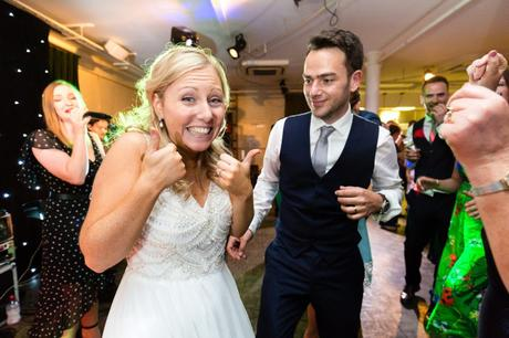 Bride gives thumbs up during evening dancing.