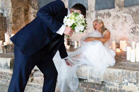 Bride laughs when shoe gets caught in her dress at Asylum wedding.