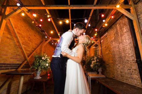 Wedding Photography at Asylum Chapel kiss under festoons at night.