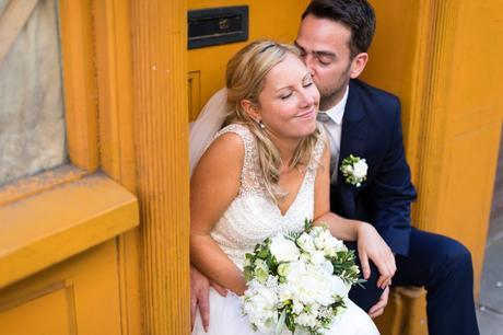 Groom kisses cute bride on the cheek at London wedding near yellow walls.