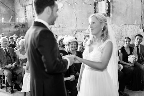 Bride's mother looks on during ring exchange at Asylum wedding.