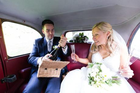 Bride and groom open champagne in car.