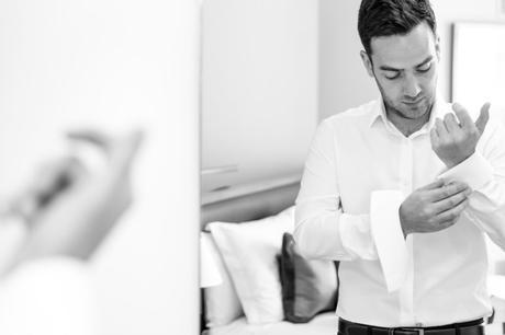 Groom buttons cuff links at Asylum wedding.