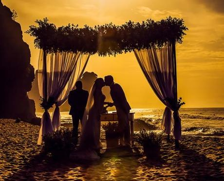 officiant prices for wedding beach newlyweds kiss