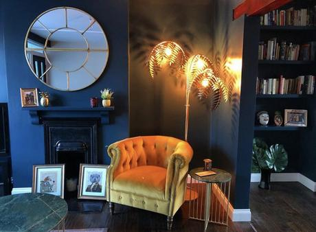 Dark and moody decor inspiration - our bronze palm leaf floor lamp styled beautifully in a navy living room.