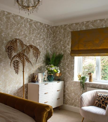 Feminine bedroom decor with patterned gold tropical wallpaper.
