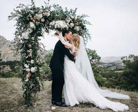 unique wedding readings newlyweds kissing near arch