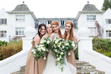 Redheaded bride having fun with bridemaids at Achnagairn Estate wedding on steps