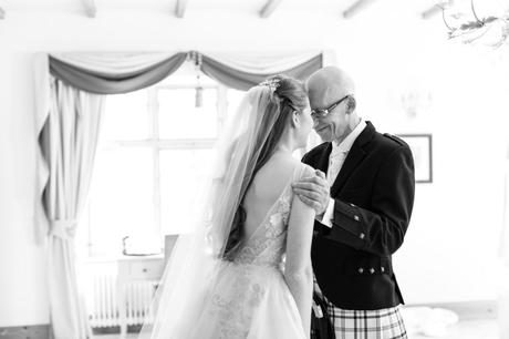 Wedding photograph of bride's father presses his forehead into bride's face as he sees her for the first time.
