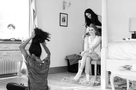 Bride having her hair styled in black and white wedding photograph