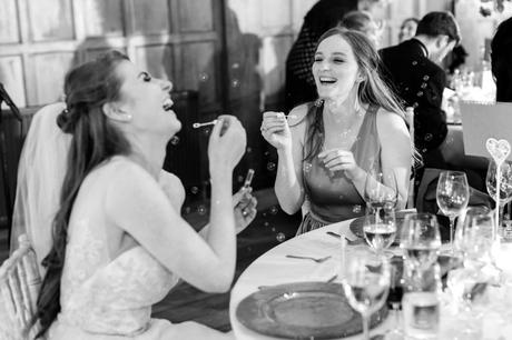 Bride and sister laughing whilst blowing bubbles at Achnagairn Estate wedding.