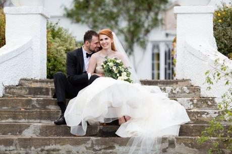 Wedding Photography at Achnagairn Estate couple with redheaded bride sitting on the steps and cuddling