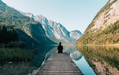 Tips To Create More Calm In Your Life - Person on a bridge near a lake