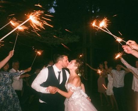 wedding party entrances ideas people raising sparklers while encircling newlyweds