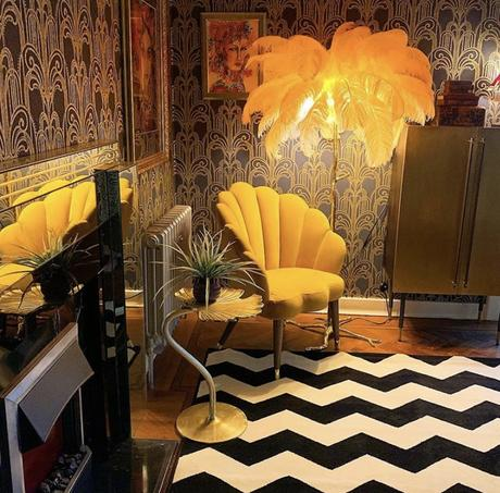 Gold ginkgo leaf occasional table styled in a glamorous and eclectic living room, with monochrome rug and ostrich feather floor lamp