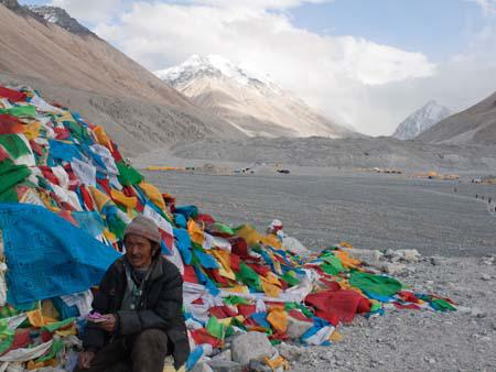 Tibetan next to some prayer flags with a cloud covered Everest in the background