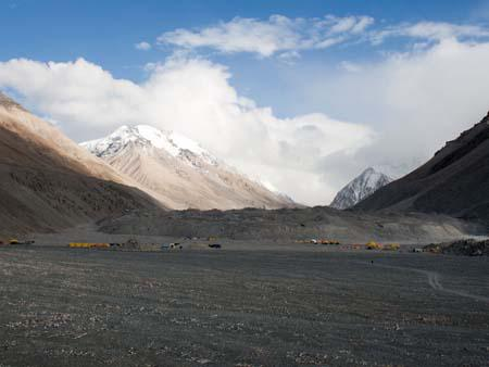 View of cloud covered Everest from Base Camp, yellow tents belong to the climbers