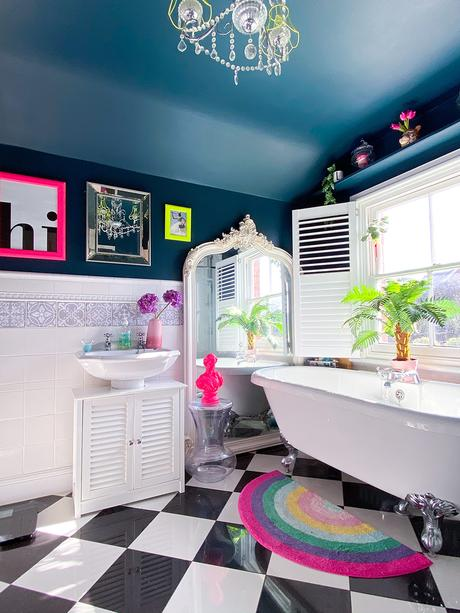 The main bathroom in this fun family home with with claw foot bathtub and quirky, neon pops of colour