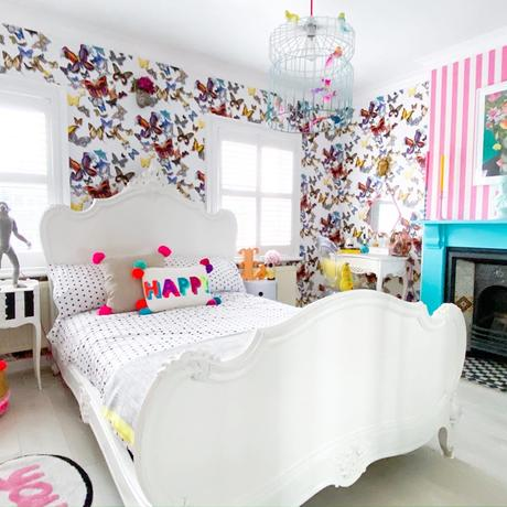 Quirky bedroom decor with butterfly wallpaper and neon pom pom cushions