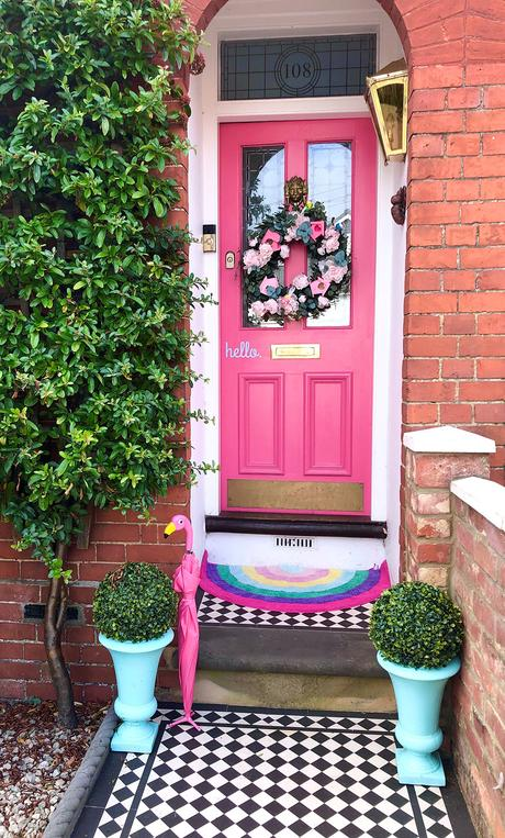 Fun family home decor - hot pink front door with monochrome floor tiles