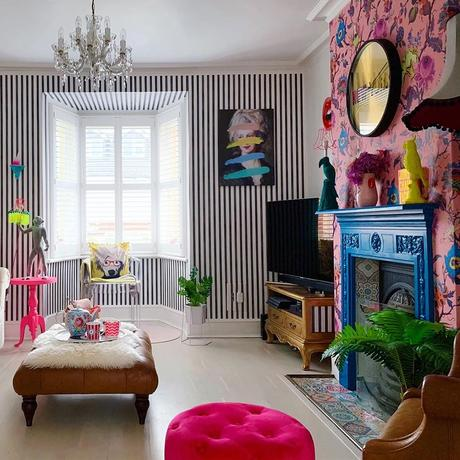 Quirky living room with colourful, clashing patterned wallpaper and cobalt blue fireplace