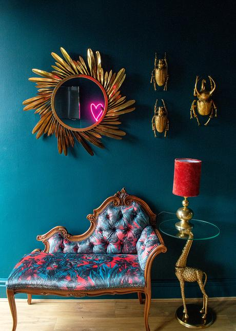 Eclectic, moody living room with golden feather mirror and quirky insect wall beetles.
