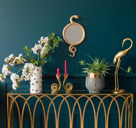 Quirky shelf styling with snake mirror and brass crane statue