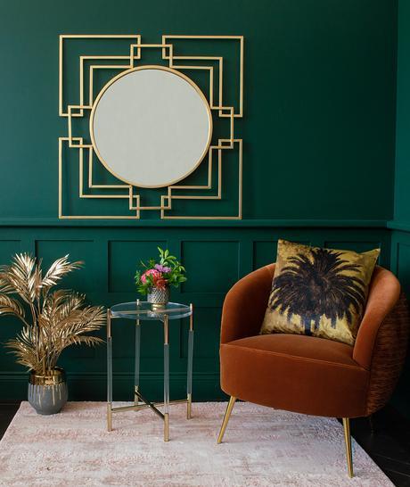 Green living room with Art Deco style statement mirror and orange velvet armchair
