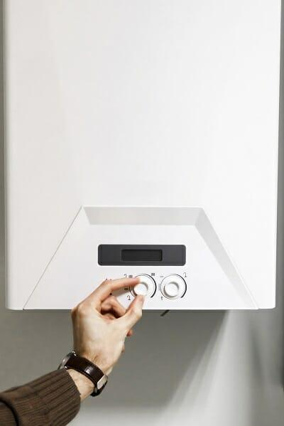 a man adjusting the output of a central heating boiler