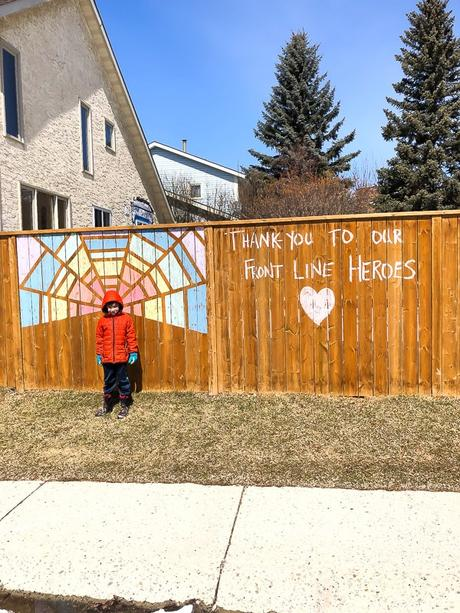 kid standing in front of fence that says 'thank you to our front line heroes'