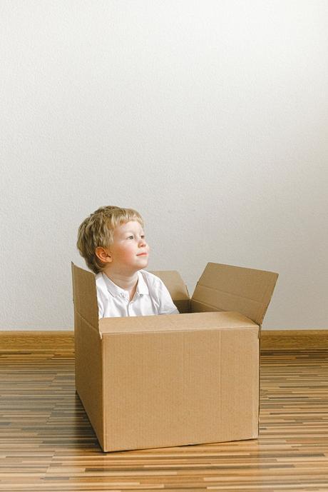 boy-in-white-shirt-sitting-inside-brown-cardboard-box-3905728-1
