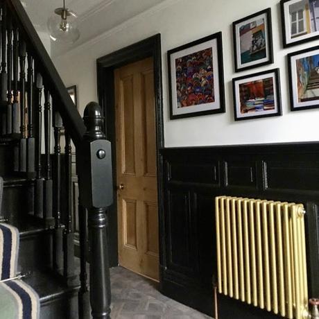 Monochrome black and white hallway with metallic gold radiator