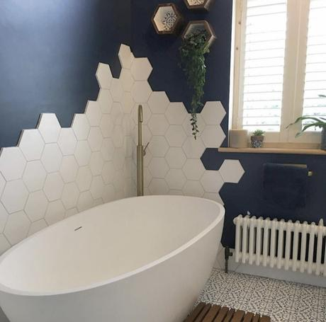Navy blue and white bathroom decor with white hexagon wall tiles and white Windsor radiator