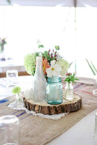 mason jars wedding centerpieces blue glass on wooden slice dan and melissa photography