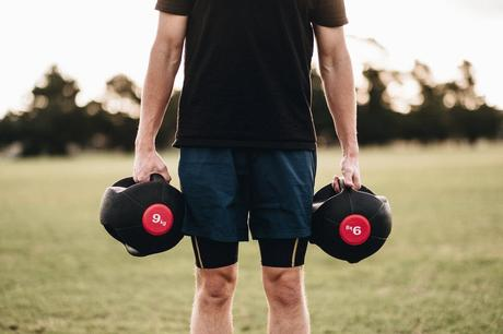 Person Holding Black Dumbbells