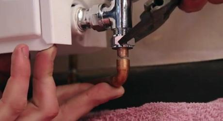 removing a radiator valve with a spanner