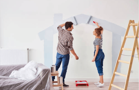 a husband and wife painting the wall of their livinf room
