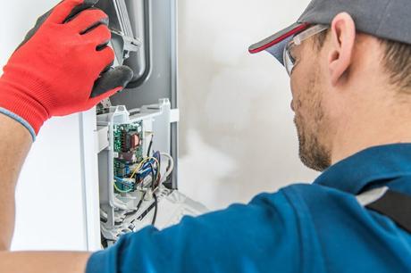 Heating engineer fixing boiler