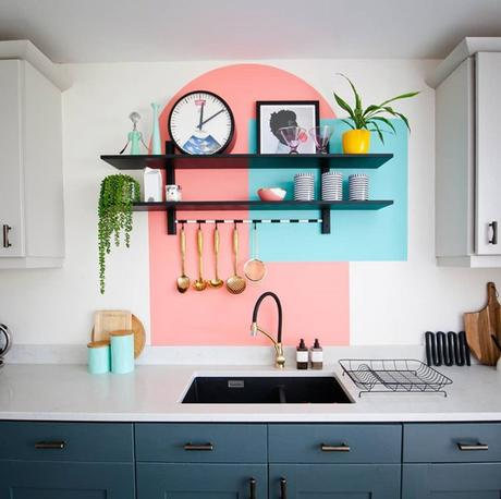 Quirky kitchen decor with colourful painted shapes behind black shelving