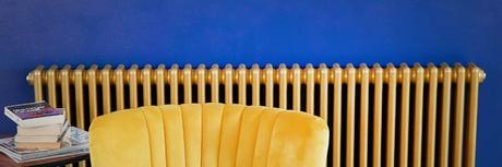 milano windsor gold radiator columns on a blue wall