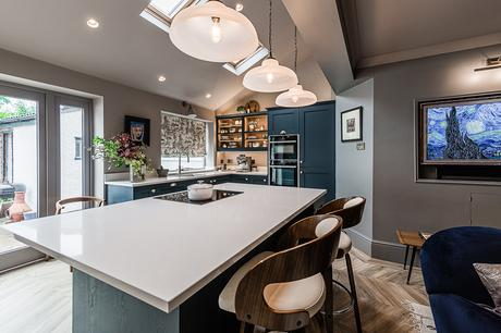 Contemporary kitchen design with navy blue cupboards, brass handles and large kitchen island
